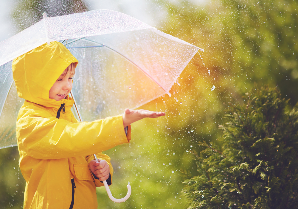 Young child in yellow raincoat with umbrella