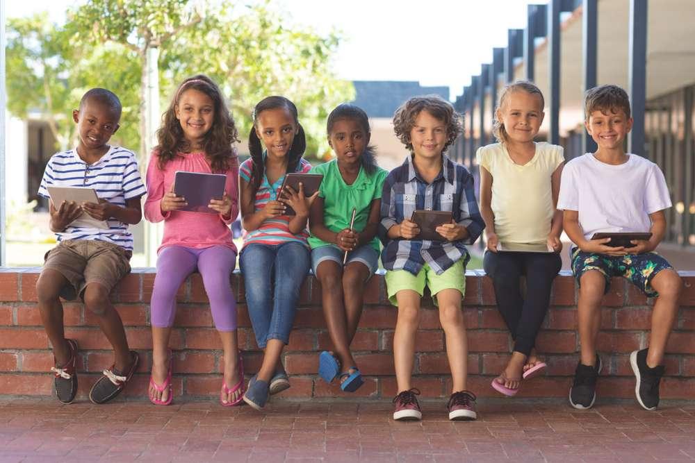 Happy kids sitting on a wall outside of school.