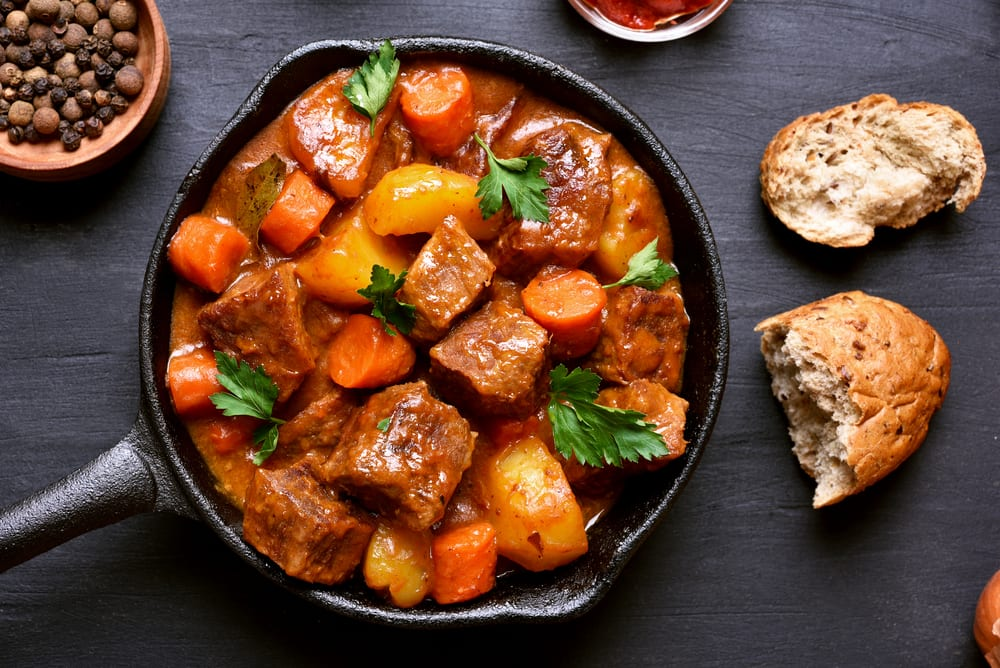 Cast iron pan of goulash with side of bread